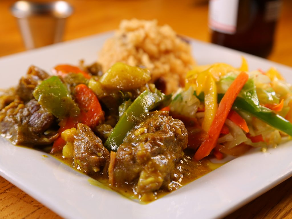 Jamaican Curried Goat with green yellow and red peppers